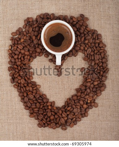 a coffee in the shape of heart on canvas with cup