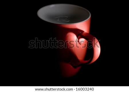 a coffee mug in the shadows with a heart shape formed by the shadows