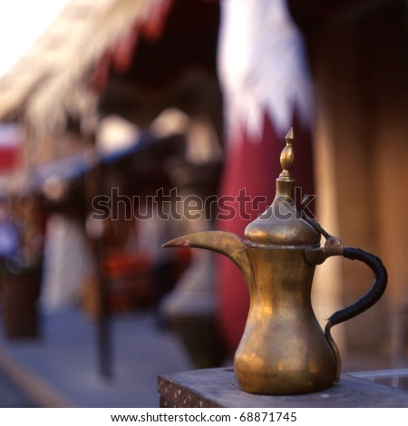 A coffee pot - the Arab symbol of welcome - in front of a Qatari flag in Souq Waqif, Doha, Qatar. The souq is one of Qatar's main tourist attractions.