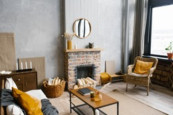 A coffee table by the fireplace of a country house and a wicker chair in the living room of the house in the Scandinavian style
