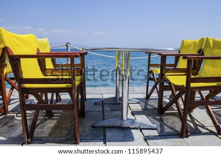 A coffee table with yellow chairs next to the beach - stock photo