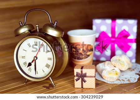 A coffee, two pastries, two present boxes and retro alarm clock