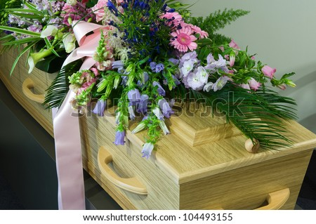 A coffin in a morgue with a flower arrangement