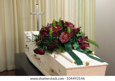 A coffin in a morgue with cross and a flower arrangement - stock photo