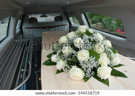 A coffin in a mourning car with a flower arrangement