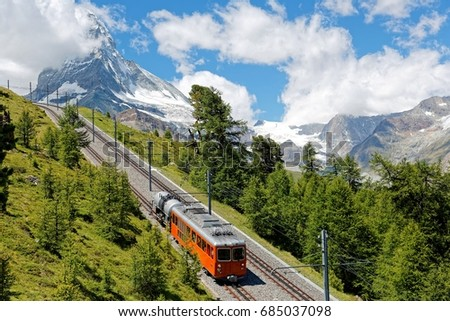 A cogwheel train traveling on Gornergrat railway through a forest by the mountainside with majestic Matterhorn mountain peak in background on a cloudy sunny summer day, in Zermatt, Valais, Switzerland #685037098