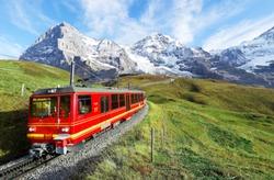 A cogwheel train travels on the railway from Jungfraujoch (top of Europe) to Kleine Scheidegg on the green grassy hillside with Eiger, Monch & Jungfrau in background in Bernese Highlands, Switzerland