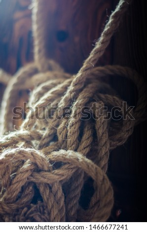 A coil of hemp rope hangs on a wooden wall in a puff of smoke. Shooting at eye level. Soft focus. Vertical image position