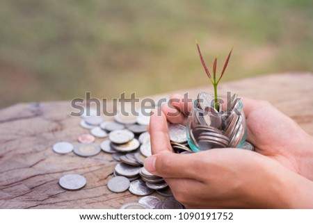 A coin in a glass bottle in the hands with a small tree on top, save money concept, Growth of business. #1090191752