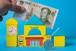 A coin in denomination of one Chinese yuan, a banknote in denomination of one Chinese yuan and a schematic bank building assembled from children's sketches