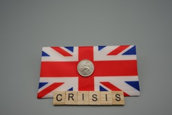 A coin over a flag of Great Britain,with a written crisis