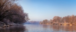 A cold morning on the Odra River in Wroclaw, the water slowly flows down the river. River bed with calm water and trees by the shore, view from the shore.