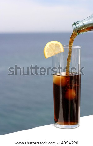 a cold refreshment at the sea, glass of cola