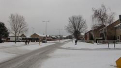 a cold winter's day in early 2010 with the road of a suburban town under the blanket of snow