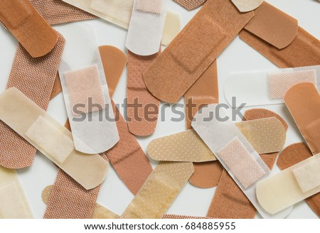 A collection adhesive bandages of various colors and shapes.