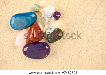 A collection of beautiful precious stones laying on sand
