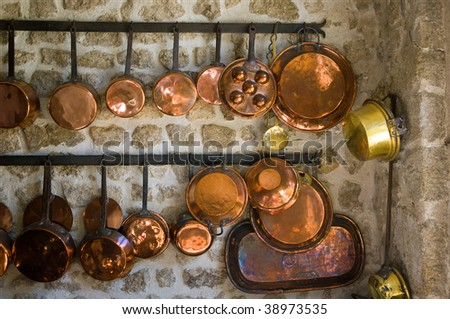 A collection of brass pans in an ancient kitchen