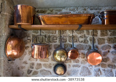 A collection of brass pots and pans in an ancient kitchen