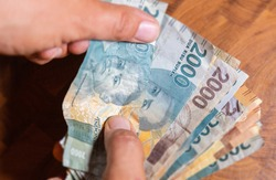 A collection of Indonesian Rupiah  banknotes in a male hand. Man hand show Rupiah the Indonesia  banknotes. Mans hands holding money of Indonesia. Asian currency. Close up to Rupiah notes.