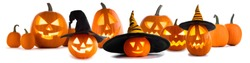 A collection of Jack O Lantern Halloween pumpkins with various different designs and witches hat in a row isolated on white background