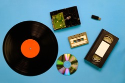 A collection of old and modern storage devices technology, Gramophone record videocassette audiocassette tape compact disk hard disk and flash drive on blue background