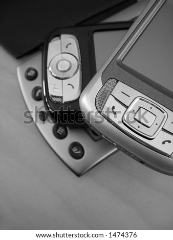 A collection of PDAs ranging from old to the newest in technology. This is a black and white image.