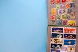 A collection of post stamps in two post albums on blue background. Top view.
