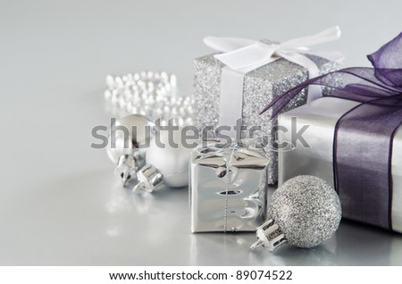 A collection of silver Christmas gifts and decorations on silver surface with soft sheen. Copy space to left.