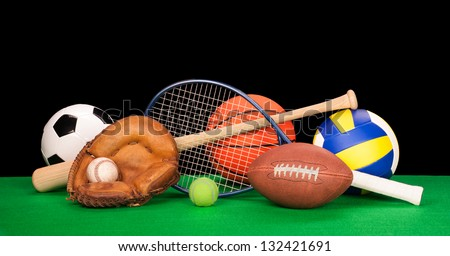A collection of sports equipment suck as a football, basketball, baseball, tennis racquet, volleyball, soccer ball and catchers glove with a black background.