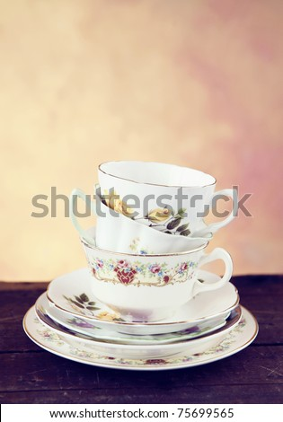 A collection of stacked antique teacups and saucers on a vintage wood table, selective focus, low key