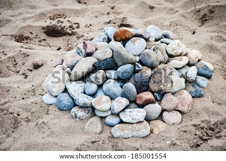 a collection of stones on sand at the beach in summertime