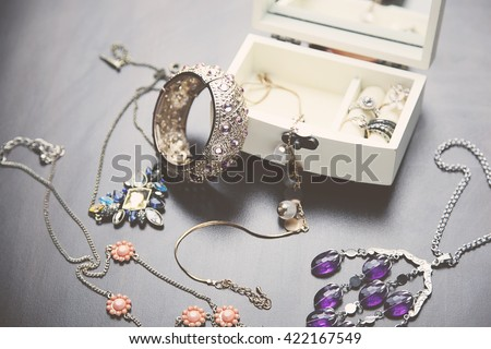 A collection of vintage jewelry in antique wooden jewelry box