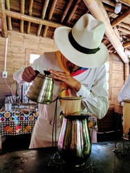 A colombian barista preparing a fresh cup of coffee at the coffee farm in Quindio, Colombia.