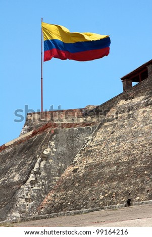 A Colombian flag is streaming in the wind over the weathered walls of the fortress of Castillo San Felipe de Barajas in Cartagena de Indias, Colombia.
