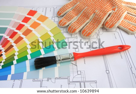 A color guide, a brush and gloves with a house plan on background