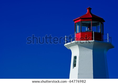 a color image of a lighthouse at Peggy's Cove, Nova Scotia, Canada. image taken in bright sunlight with contrast between the white and red lighthouse and deep blue sky