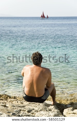 A color  photo of a caucasian man sitting on a rocky beach and watching a red sailing boat on the ionian sea in Greece.