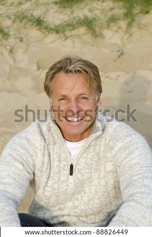 A color portrait of a happy smiling blonde haired man in his forties sitting on the beach.