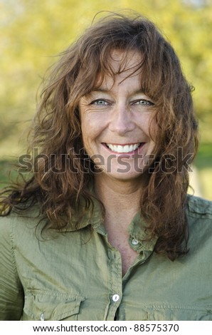 A color portrait of a happy smiling woman in her forties with brown hair and green eyes.