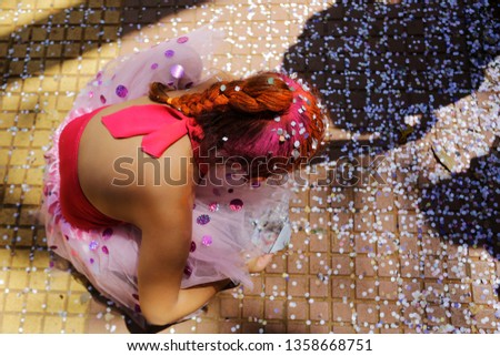 A colored hair kid play with confetti during a carnival street parade in Sao Paulo, Brazil. #1358668751