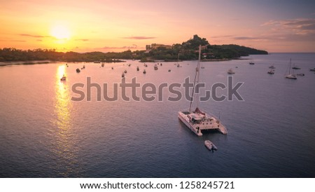A colorful aerial shot of a large white catamaran yacht anchoring in a calm bay while watching a beautiful sunset on the coast of Costa Rica in Central America.