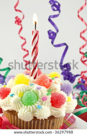 A colorful birthday cupcake, decorated with gumdrops and sprinkles, with one lit birthday candle, vertical with shallow depth of field