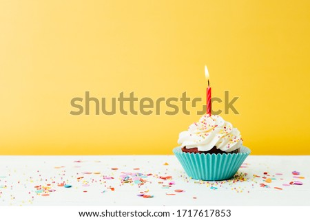 A colorful  birthday cupcake with one candle and confetti on a yellow background Foto stock ©