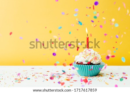 A colorful  birthday cupcake with one candle and confetti on a yellow background