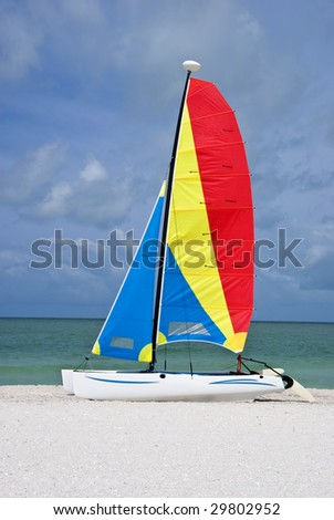 A colorful catamaran sailboat on a beautiful beach, with turquoise sea and blue sky in the background.