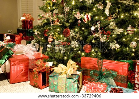A colorful Christmas tree with lots of shiny wrapped gifts, beautiful ornaments and white sparkling lights, horizontal with copy space