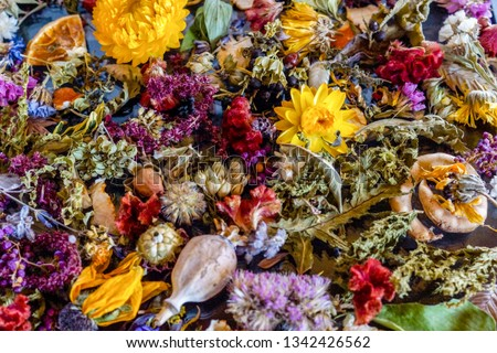 A colorful closeup of dried flowers, dried oranges, fragrant herb leaves, and seedpods used as flower confetti or potpourri