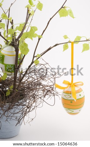 stock photo : A colorful easter decoration with plastic eggs in a flower pot on a white background