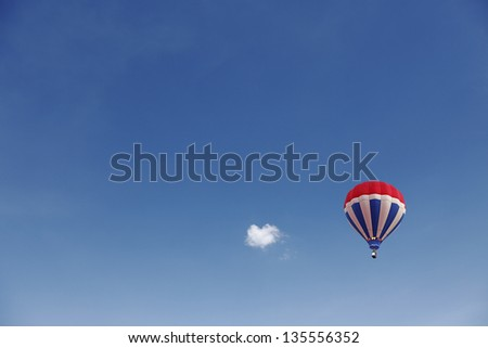 A colorful exotic hot air balloon floating in a serene blue sky with a small cloud.