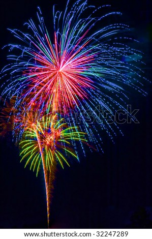 A colorful fireworks display, vertical with black background and copy space - stock photo